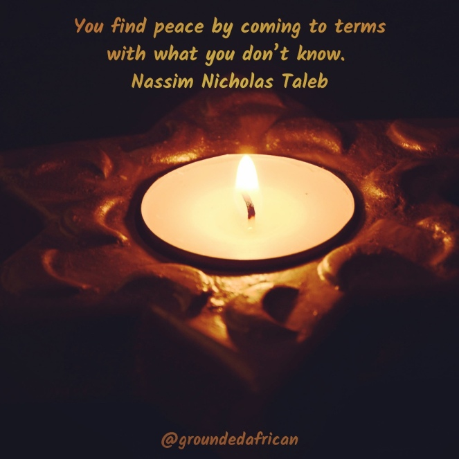 Candle burning in darkened background. Quote by Nassim Nicholas Taleb
