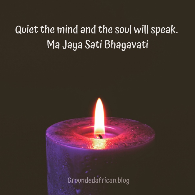 Purple candle burning in dark background. Quote by Ma Jaya Sati Bhagavati