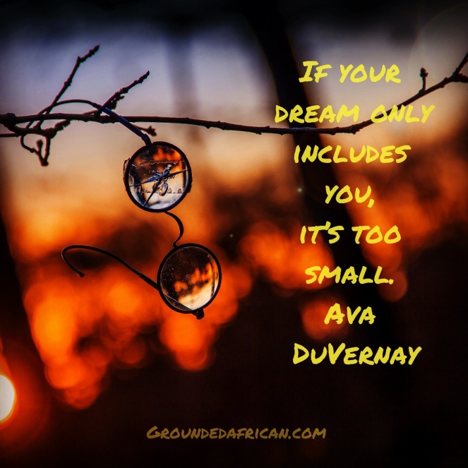 Wire rimmed round glasses hanging off branch in woods. Quote be Ava DuVernay