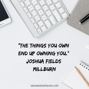 Electronic gadgets on a white table top surrounding a quote by Joshua Fields Millburn