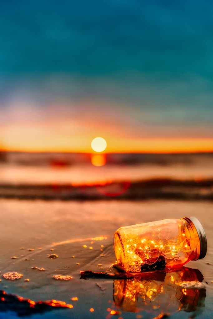 fairy lights in jar on shore at sunset
